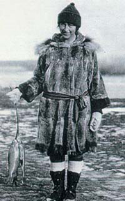 Mardy Murie in traditional Alaska Native clothing holding fish. Photo: Murie Collection